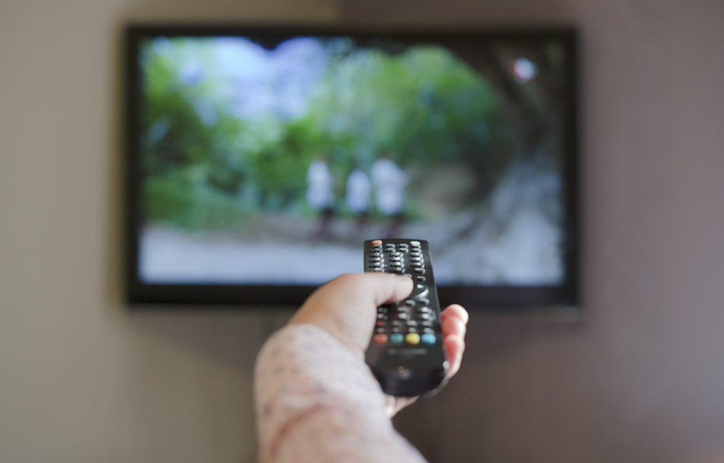 Segurando controle remoto da TV.